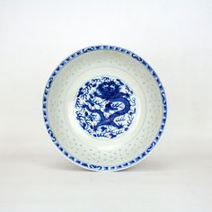 Traditionally hand crafted in China the design of these wares are commonly called rice pattern after the tiny translucent windows within the porcelain. This particular bowl measures 240mm (9 1/2 inches) in diameter by 90mm (3 1/2 inches) high and comprises of a transfer printed dragon inner centre panel rising through rice pattern hoops to a blue boarder. The outer surface of the bowl has a similar geometric top boarder descending to a small foot surrounded by a leaf design. The play of…