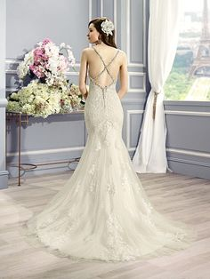 Moonlight Style H1281 Delicate embroidered lace appliques and intricate beading accents the sweetheart bodice on this mermaid silhouette. Swarovski beaded criss-cross straps dip into a low back.