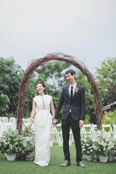 Rustic twig/branch arch with white and green florals at the base // Beautiful, Minimalist Wedding at Equarius Hotel: Alain + Pris