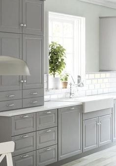 Grey cabinets, white counter, porcelain sink, lots of deep drawers - pots and dish storage?
