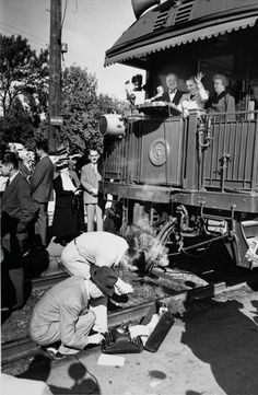 1948 ELECTION - Reporters work away as PRESIDENT HARRY S. TRUMAN, his wife Bess and their daughter Margaret wave from a train during a whistle-stop at Pocatello, Idaho, in 1948.