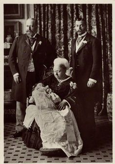 Queen Victoria with the next three generations of kings, July 1894. Behind Victoria are Albert Edward, Prince of Wales (future Edward VII) on her left, and Prince George, Duke of York (future George V) on her right. The Queen is holding in her arms...