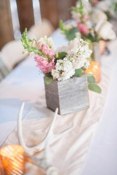 wooden boxes with floral arrangement as centerpiece with antler accent #centerpiece #weddingreception #weddingchicks http://www.weddingchicks.com/2014/02/04/cowgirl-wedding/