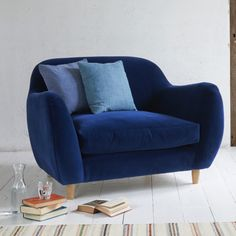 Loaf's Flapjack love-seat upholstered here in Midnight blue velvet with coordinating scatter cushions and winged arms. Cosy!