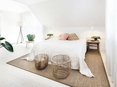chambre adulte blanche mansardée avec un grand lit et tapis