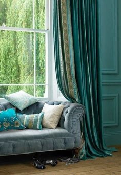 turquoise walls and draperies with a blue sofa. Love the colors of this living room.