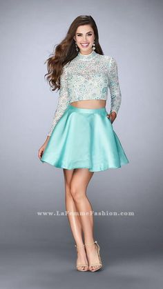 Charming short two piece with a long sleeve lace top and mikado skirt. The lace is beaded with colored rhinestones. Features an open back and a bow on the skirt with a cut out. This dress has pockets in the skirt.    White/Mint Homecoming Dress Style 24107 | La Femme