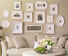 Gallery wall - love the mix of shapes (and how they hung them nice and low, tucked in near the top of the sofa)