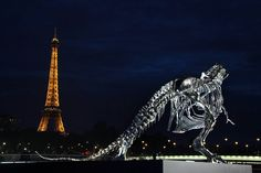 A life-size chrome-brushed aluminum skeleton of a Tyrannosaurus by French sculptor Philippe Pasqua glances back at the Eiffel Tower from a riverboat pier in Paris.