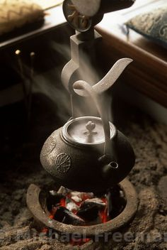 Traditional Japanese iron kettle suspended over an irori fireplece which a square-shaped hearth. Tokyo, Japan