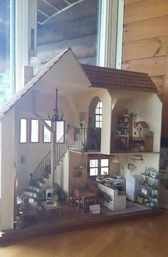 Unique Mediterranean style dollhouse. Look at that sweeping staircase!