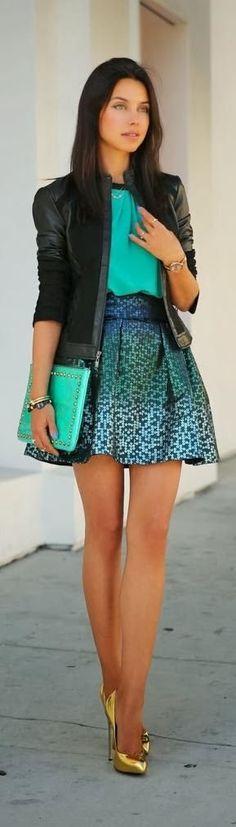 teal blouse, leather jacket, skirt, and gold pumps.