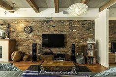 Кирпичная стена, цементный потолок, деревянные балки и стильный современный декор в интерьере красивой лофт квартиры