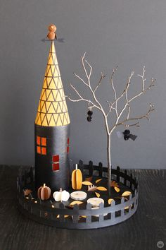 Miniature Haunted House Halloween decorations: Black tower with gold roof covered in triangle pattern, with a pom=pom owl perched on the weather vane on top. Two pop-pom bats hang from a tree, and cut-paper pumpkins and leaves are scattered in the yard. Halloween Village, Theme Halloween, Halloween Haunted Houses, Halloween Crafts For Kids, Diy Halloween Decorations, Halloween House, Holidays Halloween, Halloween Prop, Halloween Witches