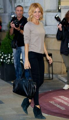Sienna Miller in an oatmeal top, black trousers, Prada tote, and Ash boot wedges