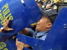 An anti-riot policeman is hit in the face with a colleague's shield by a protester (hand on L) while attempting to disperse demonstrators outside the U.S. embassy in Manila July 4, 2014. The protesters commemorated Filipino-American Friendship Day on Friday with a rally demanding the pullout of U.S. troops in the Philippines. REUTERS/Romeo Ranoco