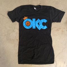 OKC Crowned Tee by DNA Galleries. Printed on American Apparel Tri-Black Unisex Track Shirt. 50% Polyester / 25% Cotton / 25% Rayon Blend. $28.00