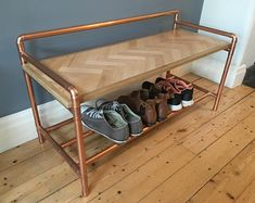 Bench with lower storage shelf in a retro industrial style with a copper pipe frame and reclaimed hard wood herringbone inlay