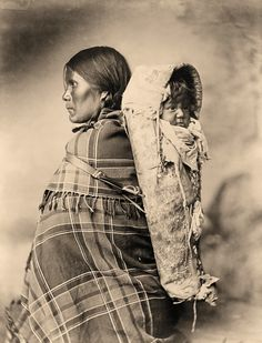 The Utes traditionally made cradleboards out of willow, but the reservation period began a trend of inserting boards into buckskin sacks, like the cradleboard holding Peearat's baby in this 1899 photograph.  – Courtesy Library of Congress –