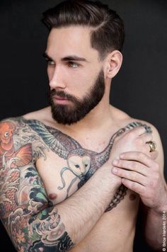 Great profile of this bearded man and his owl chest tattoo!