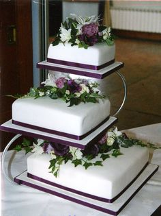 Could change ribbon to pink and have flowers as white cala lily and pink rose with greenery + couple made from icing sat on top tier
