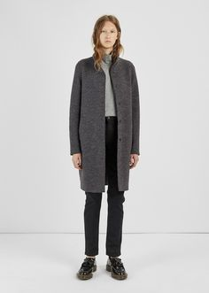 Grey rounded coat with subtle mustard yarns for a muted melange effect, crafted in military-grade felt with an optional standing collar. Rounded cocoon fit.