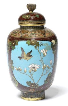 A cloisonné enamel ovoid jar and cover By Namikawa Yasuyuki, early Meiji Period Worked in silver wire, the body decorated with three panels enclosing either a bird or butterflies in flight over autumnal plants and flowers, on pale blue grounds, reserved against a speckled reddish-brown ground of chrysanthemum heads and stylised foliage, the shoulder and foot with a band of formal lappets, applied with a gilt bronze rim and foot, the cover surmounted by a gilt kiku-finial