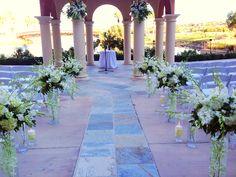 Enchanted Florist ceremony decor- centerpieces as aisle decor, orchids, hydrangeas, candles
