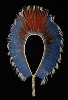 Feather wheel, Brazil, Kaiapó, late 20th century.  The feather wheels of the Brazilian Kaiapó Indians are one of the most spectacular feather objects of the entire Amazonas region. It is a so-called occiput feather wheel and is worn exclusively by the women at the solemn ceremony of name-giving, when children are accepted into the Kaiapó community.  Feather wheel; Tail-feathers of the scarlet Ara and the Aracangá, cotton thread;  Brazil, Kaiapó, late 20th century. h 160 cm. Photo: A. Dreyer.