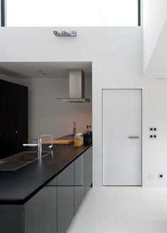 Moderne binnendeur zonder omlijsting. Witte deur in combinatie met witte muren, een witte PU vloer en een zwarte moderne keuken.
