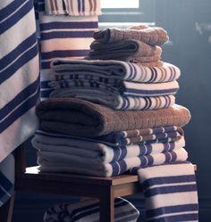 Närbild av en hög med randiga och enfärgade handdukar på en stol.