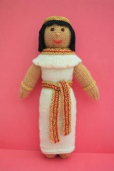 Doll Knitting Pattern - Menet - An Egyptian Princess Doll  by Joanna Marshall This is Menet, an Egyptian Princess Doll 1300 BC. Menet is a knitted Egyptian doll and is 28cms tall. The doll is knitted in Double Knitting Wool & Anchor Artiste Metallic Gold/ Red Thread. This knitting pattern is Worked Flat.  Linen was the most popular material used for Ancient Egyptian clothing. It was comfortable & kept the wearer cool, due to the desert heat.   Clothes were decorated with jewels, regardless…