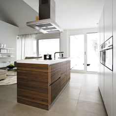 The walnut finish on the bulthaup b1 fronts provides a touch of contrast and warmth to this living space. www.bulthaup.com #bulthaup #kitchens #modernkitchens