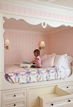 """Fairytale Girl's Bedroom. The pale pink and cream beadboard of the alcove enclose the bed in classic lines and feminine colors. Folding sconces promise optimal reading light, and the blue-and-pink patterned quilt adds sweetness."""""""