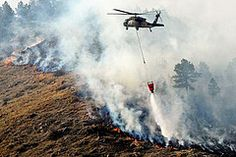 A South Dakota Army National Guard UH-60 Black Hawk helicopter drops 600 gallons of water on a fire in Rapid City, South Dakota.