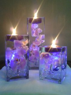 A set of three square vases with purple orchids floating in water perfect for unique Beach Wedding Reception Centerpieces
