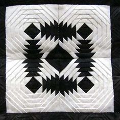 """Close up of central motif - Crazy in Black & White, by Geraldine Nall. This quilt is small, perhaps a foot on each side. From the artist's statement, """"It has 6,300 pieces and consists of 140 1.5″ and 2.5″ square pineapple blocks."""""""