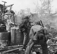 Got his back: While under fire, U.S. Marines advance on occupying Japanese forces in Tanapag, Saipan in June 1944