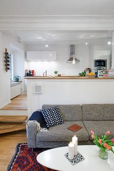 modern white kitchen with lots of light and a living room with cozy textiles and upholstery
