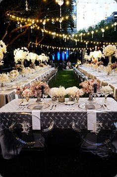 Garden party wedding reception with monogramed chairs, lace tablecloths, swag lighting.