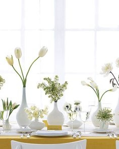 Petite white vases of white flowers on white table cloth.