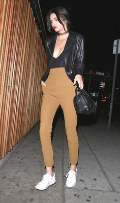 Kendall Jenner wears tan pants, a black leather jacket and white sneakers