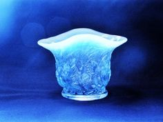 "Vintage Chanticleer Vase.  This blue opalescent glass vase was made by Duncan and Miller around the 1930's.  The pattern is Chanticleer.  Chanticleer was the name of a rooster in a fable dating to the Middle Ages.  It was also included in Chaucer's Canterbury Tales.  This blue vase features roosters or Chanticleer all around it.  The vase is approx. 4 3/8"" across, 3 1/4"" tall and 3"" wide.  It is in great condition with no chips or cracks."
