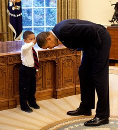 Little boy rubbing Obama's head to feel if presidential hair feels the same like his. Obama happily obliged.