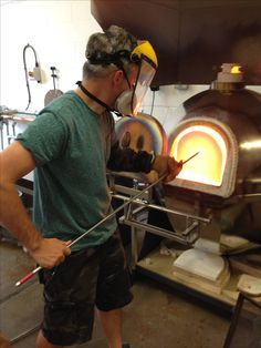 Charging the furnace with glass batch for glass blowing at Rothschild & Bickers studio in Hertford