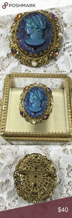 Vintage Iridescent Blue Glass Cameo Brooch Large iridescent molded blue glass cameo, surrounded by blue carved glass flowers and flourishes, ornate gold tone frame with faux pearls and Aurora Borealis rhinestones, filigree gold tone back. Vintage Jewelry Brooches