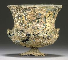 "A ROMAN ""SPLASHED"" GLASS CARCHESIUM  CIRCA 1ST CENTURY A.D.  Transparent cobalt blue in color, free-blown, the surface embellished with applied opaque white and yellow patches, with a rounded bowl, carinated shoulders and tall flaring walls, the rounded rim folded out then in, and encircled by an applied opaque white trail, on a low hollow conical foot, with twin opposed vestigial handles, the surface now highly iridescent  4 7/8 in. (12.4 cm.) high"