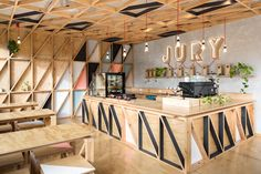 Pastel-coloured wedges pattern the light wooden walls of this cafe in a former prison by Australian office Biasol: Design Studio