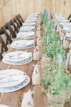 #theinspiredtable Simple lavender table centerpieces in moss and twine pots. Wooden table and chairs.