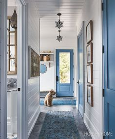 Bold blue hues pair well with grey limestone floors in Sarah Richardson's mudroom, where radiant in-floor heating lets pup Daisy get warm and cozy. Beach Cottage Style, Beach Cottage Decor, Architrave, Hallway Decorating, Cottage Decorating, Decorating Ideas, Painted Doors, Coastal Homes, Beach Cottages